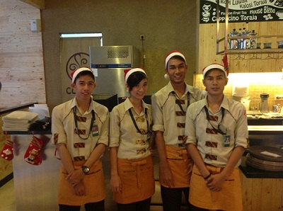 Baristas at a coffee joint in Palembang's ritziest mall sport  Santa hats for the holiday season. And are those stockings hanging from the counter behind them? (Dustin Volz/Indonesiaful)