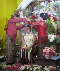 The groom's turn: almost finished with his portion of the Siraman ceremony, the groom-to-be smiles as his parents bathe him in water and flowers. (Gillian Irwin/Indonesiaful)