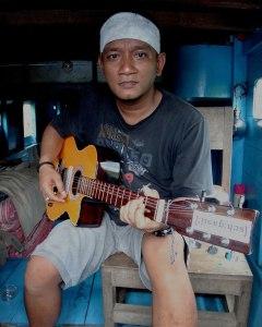 Cigarette in hand, Erwin strums his guitar during a klotok tour through Tanjung Puting National Park, Kalimantan. (Emily Denny/Indonesiaful)