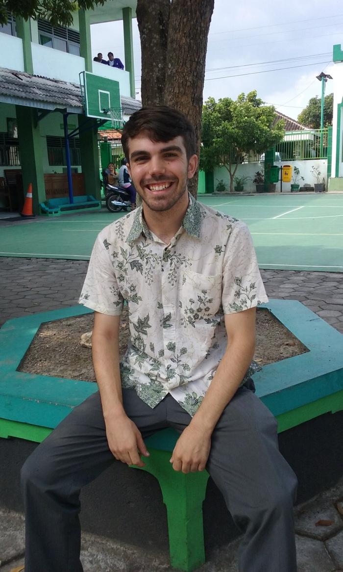 Bryan Howard, placed in Wonosari, D. I. Yogyakarta, sporting some green, leaf-motif batik outside MAN Wonosari's teachers' room.