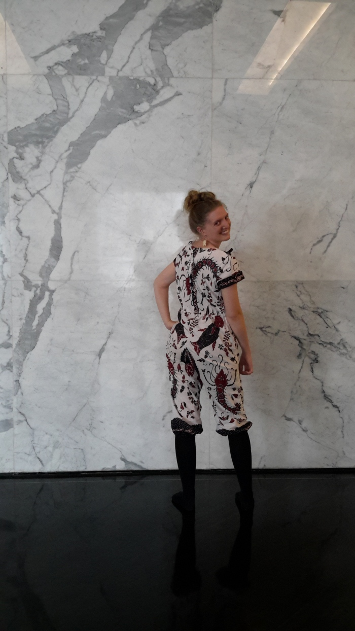Clara Summers, placed in Malang, is modeling a custom-tailored batik romper. The fabric is from Madura and features sea life motifs. Look closely and you'll see shrimp and fish in the batik pattern.