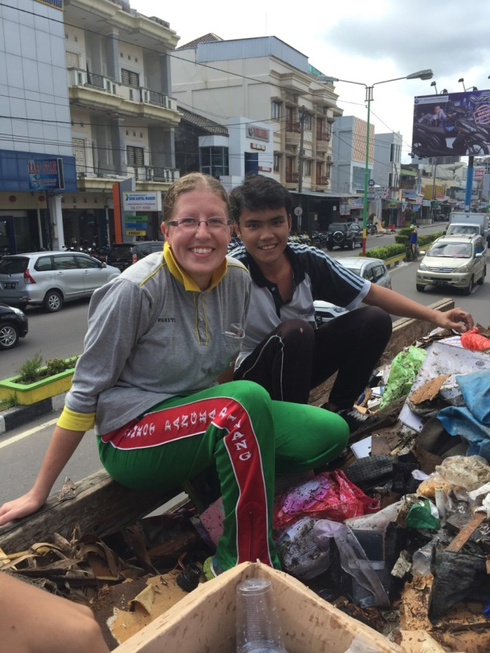 Caitlin with one of her students. They are riding the fully-loaded dump truck through the streets of Pangkal Pinang and out to the dump station in a village on the outskirts of town.