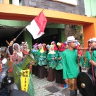 Class 12 Social 1 is dressed and ready to hit the streets. The students dressed up their walikelas [homeroom teacher] as a cavewoman riding a dinosaur (left). The class is carrying their patrol instruments out the parade route (right) and the dancers follow closely behind (center).