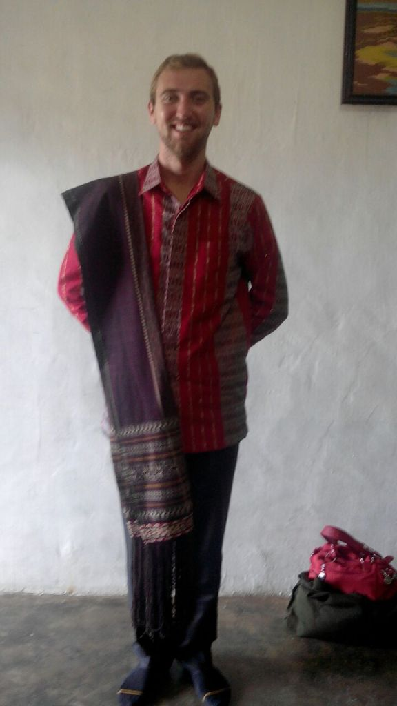 Daniel Gerardi, currently living in Balige, North Sumatra, is wearing in formal Batak clothing. Batak refers to a variety of ethnic groups native to North Sumatra. Daniel's shirt is a typical Batak design and the fabric draped over his right shoulder is of particular significance among the Batak community. This kind of woven fabric is known as Ulos. There are different types of Ulos meant to be used as part of different ceremonies. The one pictured here is Ulos Sirara, worn by Batak men to weddings and funerals.
