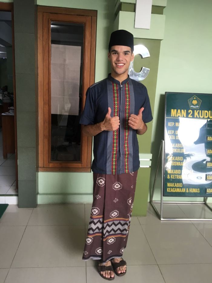 "Grant ""Vinny"" Owen wears a sarong, baju koko, and peci in his daily life in Kudus. This is a typical outfit worn by men in Indonesia, particularly in Java, that is associated with their Muslim identity. This outfit is typically worn to the mosque or at any religious event. In Kudus, the sarong [skirt] and peci [hat] are worn in the community as daily wear. The peci is traditionally associated with Islam, but non-Muslim men may also wear it as it is the national hat of Indonesia. Although Vinny is not Muslim, he regularly wears this traditional outfit because he teaches as MAN 2 Kudus, a Muslim high school, and because the surrounding community is predominantly Muslim."