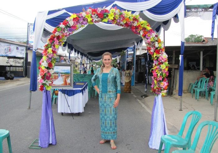 Kelly Fitzgerald is standing at the entrance to a friend's wedding wearing a complete batik outfit. The fabric for this outfit is from Kalimantan and is printed batik with shiny accents. It was a birthday gift from her neighbors in Pangkal Pinang during her first year in Indonesia. Using the fabric, she had a modern kebaya and matching skirt made to be worn as formal wear. A kebaya is a style of blouse for women that are most often associated with Javanese culture. Now that Kelly lives in Surabaya, East Java, she earns much praise from her new friends whenever she wears it to weddings or parties.