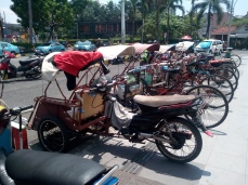 "A bentor is a play on words combining ""becak"" and ""motor."" A bentor driver rides on a motorcycle and the passenger(s) sit in a covered buggy in front."